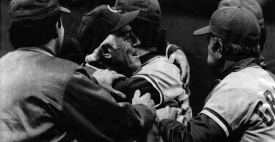 Cincinnati manager Sparky Anderson hugs pitcher Rawley Eastwick. At right is Reds coach Alex Grammas.