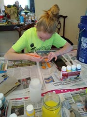 Mackenzie Carson, 14, Cleves paints rocks in several different designs to drop off during her paper route every Wednesday.