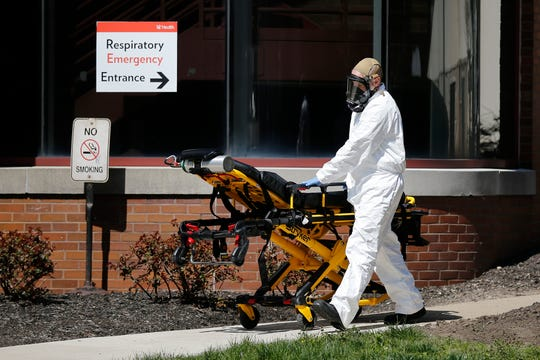 A Cheviot Fire Department EMT returns a used stretcher to his ambulance while wearing full coveralls and mask outside the emergency entrance at the University of Cincinnati Medical Center in the Avondale neighborhood of Cincinnati on Thursday, April 2, 2020.