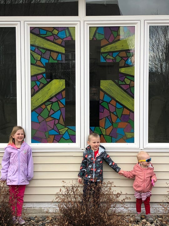 """Avelia, Matthew and Francesa Kurth of Urbandale show off their newly painted """"stained glass window,"""" through which light will shine as they join streaming Mass each Sunday and throughout the Easter season."""