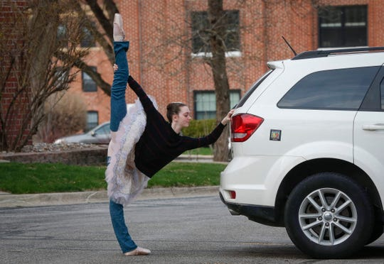 Ballerina Lily Ungs, 17, of Urbandale, warms up before performing a ballet dance in the parking lot of the apartment complex on Grand Ave. where her grandparents, Jon and Elaine Lindgren, live in Des Moines on Wednesday, April 1, 2020.