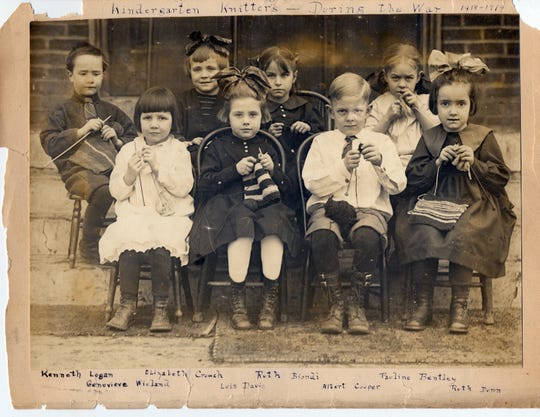 """This 1918 photo shows a group of students at Oak Park school in Des Moines. A handwritten note reads """"Kindergarten knitters during the war."""""""