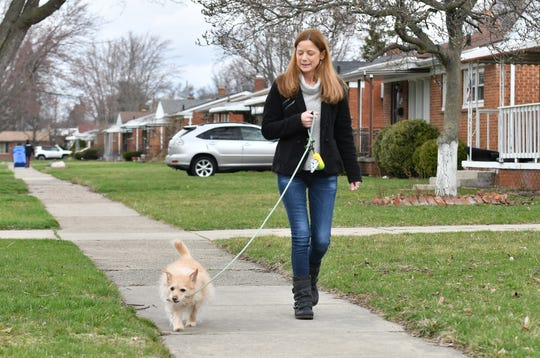 Lori Schubring, 45, walks her dog, Jack, near her home in Warren on April 2, 2020. Schubring has progressive multiple sclerosis and has been staying very close to home.