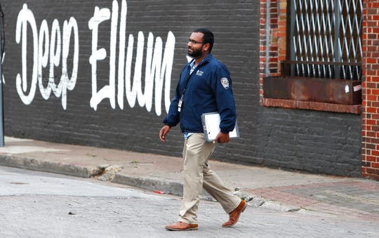 In this March 31, 2020, file photo, City of Dallas code compliance officer Eldho Babu checks on businesses amid concerns of COVID-19 spreading in the Deep Ellum section of Dallas.