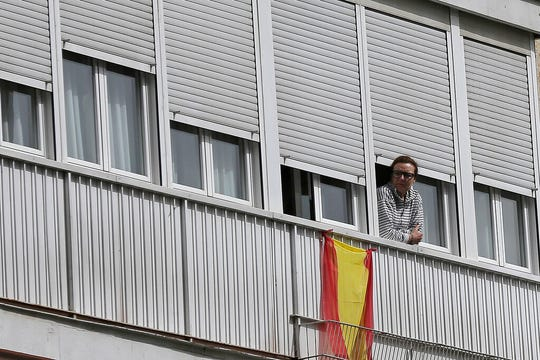 In this March 19, 2020, file photo, a woman looks out from a balcony next to a Spanish flag in Madrid, Spain. Residents are snitching on businesses and neighbors as authorities worldwide work to enforce business shutdowns and stay-at-home orders meant to limit person-to-person contact amid the coronavirus pandemic.