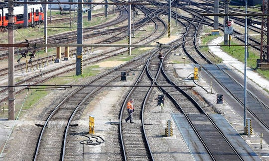 A railroad employee walks over the tracks in Vienna, Austria, Tuesday, March 24, 2020.