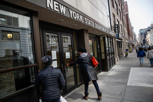 Visitors are unable to gain access to the Department of Labor due to closures over coronavirus concerns, in New York. Applications for jobless benefits are surging across the country.