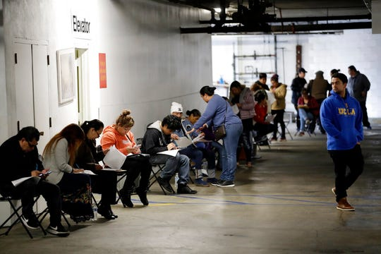 In this March 13, 2020 file photo, unionized hospitality workers wait in line in a basement garage to apply for unemployment benefits at the Hospitality Training Academy in Los Angeles.
