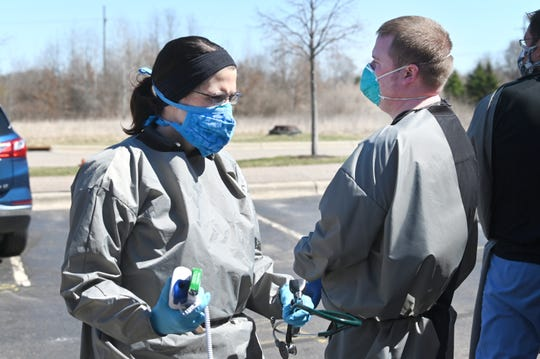 Dr. Danielle Leslie carries the COVID-19 test given to a drive-up resident at the Mobile Care Unit outside the Clarkston Medical Group on Thursday, April 2, 2020