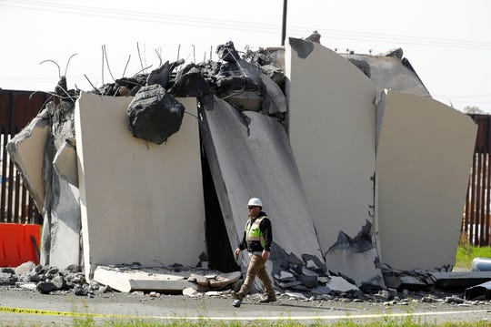 In this Feb. 27, 2020, file photo, a worker passes a partially-demolished border wall prototype during demolition at the border between Tijuana, Mexico, and San Diego. Major construction projects moving forward along the U.S. borders with Canada and Mexico amid the coronavirus pandemic are raising fears workers could spread the sickness within nearby communities.