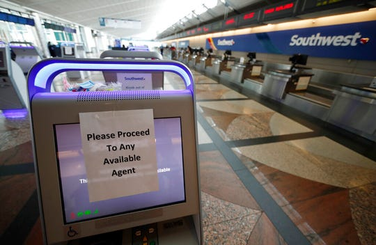 A paper sign covers the screen of a self check-in kiosk directing passengers to where agents wait at an empty Southwest Airlines ticket counter at Denver International Airport as a statewide stay-at-home order remains in effect in an effort to reduce the spread of the new coronavirus Wednesday, April 1, 2020, in Denver.