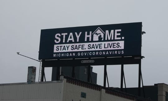 "An electronic billboard in downtown Lansing encourages residents to ""stay home"" amid the COVID-19 pandemic."