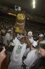 Mateen Cleaves hoists the 2000 championship trophy.