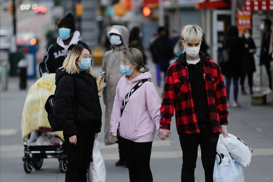 Pedestrians wear personal protective equipment as they walk along Main Street Wednesday, April 1, 2020, in the Flushing section of the Queens borough of New York.