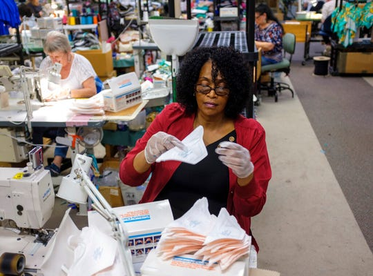 Debbre Robinson removes old elastic from medical masks for re-sewing with new elastic Monday, March 30, 2020 in Conway, S.C . The Tara Grinna Swimwear factory in Conway converted their operations from making custom swimsuits to sewing elastic into N95 masks in response to the coronavirus outbreak.