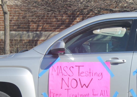 """A protester wearing a medical mask drives around downtown Lansing on Thursday, April 2, 2020. A sign taped to the vehicle calls for """"mass testing now."""""""