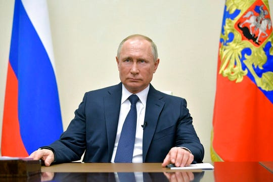 Russian President Vladimir Putin addresses Russian citizens on the State Television channels at the Novo-Ogaryovo residence outside Moscow, Russia, Wednesday, March 25, 2020. Putin has ordered most Russians to stay off work until the end of the month to curb the spread of the coronavirus.