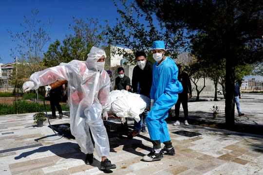 People wearing protective clothing carry the body of a victim who died after being infected with the new coronavirus at a cemetery just outside Tehran, Iran, Monday, March 30, 2020.
