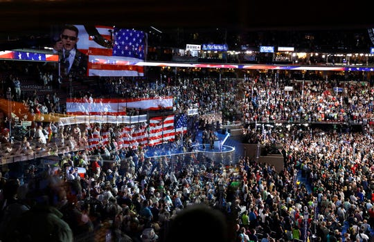 In this July 26, 2016, file photo the stage is reflected on a glass window on the suite level at Wells Fargo Arena as Timmy Kelly sings the national anthem before the start of the second day session of the Democratic National Convention in Philadelphia. The coronavirus pandemic is forcing Democrats and Republicans to take a close look at whether they'll be able to move forward as planned this summer with conventions that typically kick off the general election season.