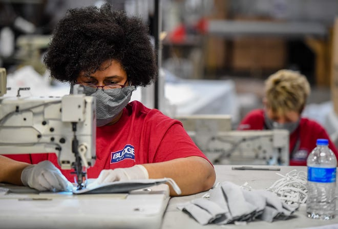 Workers at Henderson's Budge Industries, Lauretta Stewart-Dlanks, left, and Crystal Baxter attach the elastic straps for medical masks as workers at the plant convert to making masks instead of their usual products, car and RV covers Wednesday, April 1, 2020.