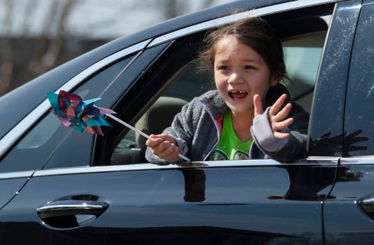 Callie Riley, 7, waves to Harper DeVous, 5, as she passes by as part of a birthday parade outside her McCutchanville, Ind., home Thursday morning, April 2, 2020. The five-year-old was planning her first-ever birthday party, but the coronavirus pandemic put the brakes on that plan, so her friends threw a parade for her.