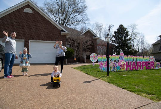 Harper DeVous, 5, second left, and her family, from left, Sam, dad, James, 2, Jaimee, mom, and Mason, 3 weeks, wave to the birthday parade the youngster's friends created outside her McCutchanville, Ind., home Thursday morning, April 2, 2020. The five-year-old was planning her first-ever birthday party, but the coronavirus pandemic put the brakes on that plan, so her friends threw a parade for her.