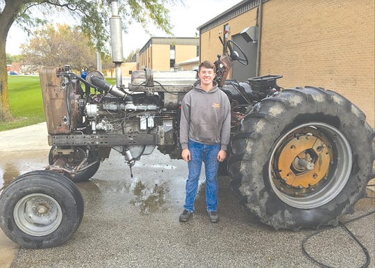 Brayden Evans, a member of South Hamilton FFA, Ellsworth, IA, and his 1967 Farmall tractor restoration (his grandfather's tractor), before.