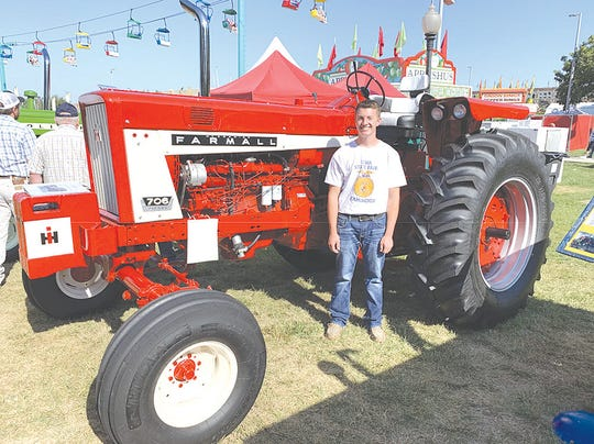 Brayden Evans, a member of South Hamilton FFA, Ellsworth, IA, and his 1967 Farmall tractor restoration (his grandfather's tractor), after.