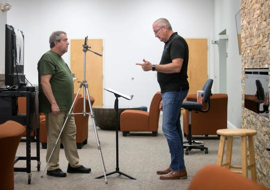 Don Palmer, left, helps Pastor Gary Cox of First Christian Church of Fort Myers record a segment of his Sunday worship service on Wednesday, April 1, 2020.