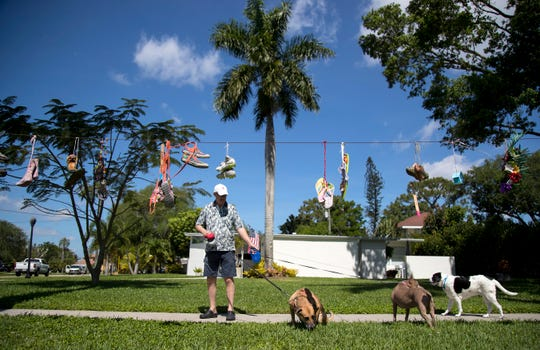 """John Anderson walks his dogs by his neighbor Annette Brown's house on Wednesday, April 1, 2020, in Fort Myers. Brown, who is an artist, came up with the idea to decorate shoes with inspirational messages and is encouraging her neighbors and friends to do the same. Brown got the inspiration from Romans 10:15 - """"How beautiful are the feet of messengers who bring us good news!"""""""