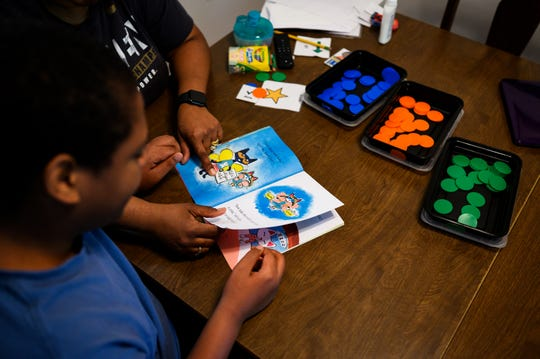 Diquaris Johnson follows along as Valerie reads out loud to him at their Mauldin home Thursday, April 2, 2020. Diquaris, a speical needs student, had to transition to at-home learning because of school closures across the state due to the novel coronavirus pandemic.