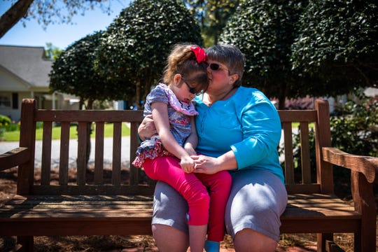 Denise Barrett kisses her daughter, Abby, 11, who has Walker-Warburg syndrome, in a courtyard in their neighborhood in Anderson Thursday, April 2, 2020.