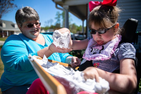 Denise Barrett helps her daughter, Abby, 11, who has Walker-Warburg syndrome, as she plays with shaving cream on a tray attached to her wheelchair, at their home in Anderson Thursday, April 2, 2020.