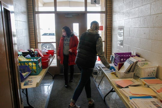 Sharman Ameline (left), a 1st grade teacher at Loy Elementary School, and Kara Greenwell, a literacy and math specialist, sort through materials at at the remote learning packet pick up on April 2, 2020.