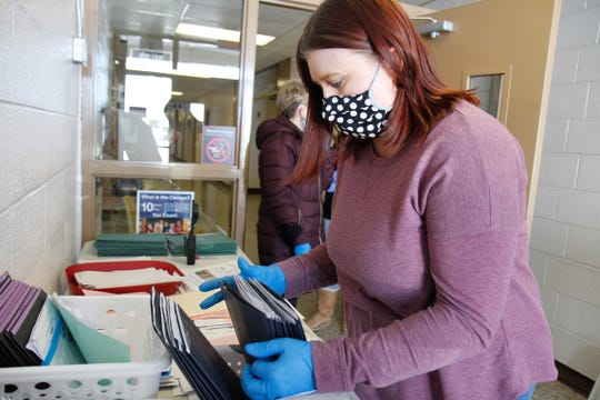 Alicia Dickman, a kindergarten teacher at Loy Elementary School, sorts through packets for the next parent in line at the packet pick up drive-thru on April 2, 2020.