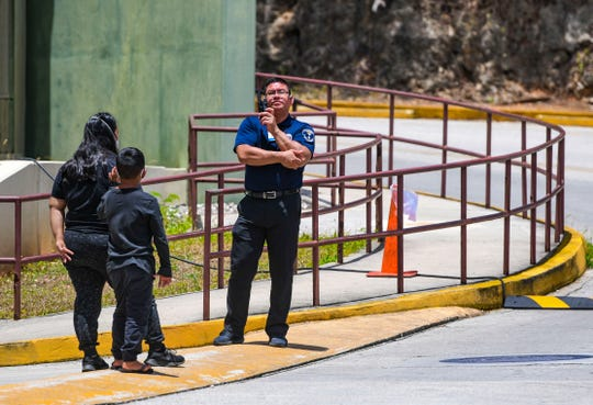 Security officer Vicente Guerrero, right, uses a two-way radio to communicate with other hospital personnel prior to allowing potential patients beyond the stage one checkpoint, near the emergency room entrance of the Guam Memorial Hospital in this April 2 file photo.
