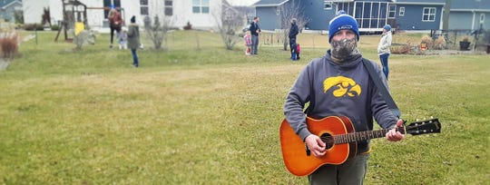 """In one North Liberty neighborhood last week, neighbors gathered in their back yard, following proper social distancing, to group sing Bon Jovi's """"Livin' on a Prayer"""" anthem of hope. Tony Hakes is pictured here with guitar."""