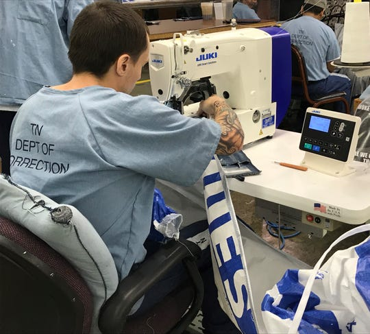 An inmate at the West Tennessee State Penitentiary in Henning uses a sewing machine to make masks and gowns to help slow the spread of COVID-19.