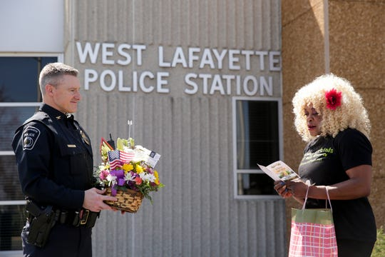 Paula Davis, owner of Blooms and Petals Fresh Flowers and Event Concepts, reads a card from the flower bouquet being donated to the West Lafayette Police Chief Troy Harris and the department, Thursday, April 2, 2020 in West Lafayette.