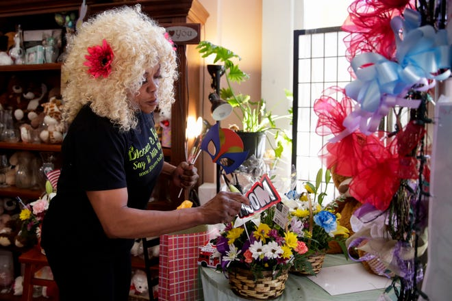 Paula Davis, owner of Blooms and Petals Fresh Flowers and Event Concepts, adjusts an arrangement being donated to workers on the front line of the Covid-19 pandemic, Thursday, April 2, 2020 in Lafayette.