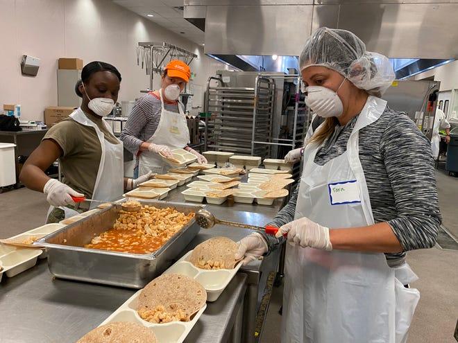Volunteers at Second Harvest Food Bank prep hot meals.