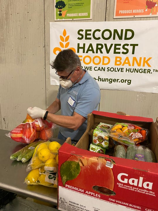 A volunteer packs a box of produce at Second Harvest Food Bank.