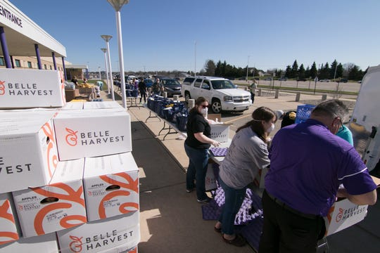 Gleaners Food Bank volunteers package and load food in cars lined up around the perimeter of the Fowlerville High School parking lot Thursday, April 2, 2020.