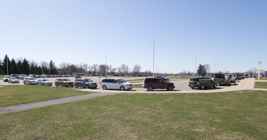 Cars line up to accept food from Gleaners Food Bank at Fowlerville High School Thursday, April 2, 2020.