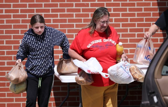 Cindy Stubbs, right, and her granddaughter Kynnedy Carta, 10, carried bags of meals provided to them at the Hope Southern Indiana food bank in New Albany, In. on April. 2, 2020.  The agency has been providing donated food and toiletries to the public after most businesses have closed due to concerns over the coronavirus pandemic.