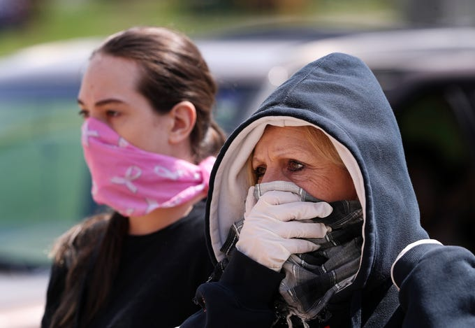 Deborah Niehaus, right, and her daughter Amelia Niehaus, 21, used scarves and bandanas for face protection as they waited at the Hope Southern Indiana food bank in New Albany, In. on April. 2, 2020.  The agency has been providing donated food and toiletries to the public after most businesses have closed due to concerns over the coronavirus pandemic.