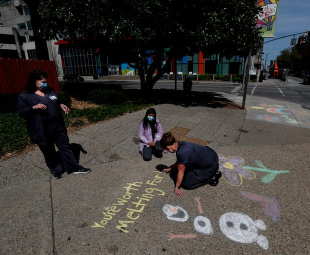 Beth Jewell, an EM Tech, creates art with chalk on a sidewalk in the downtown hospital district. 