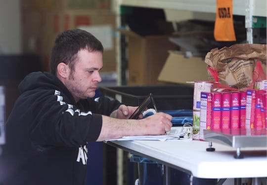 Aaron Travelstead took inventory of donated food and toiletries at the Hope Southern Indiana food bank in New Albany, In. on April. 2, 2020.  The agency has been providing the goods to the public after most businesses have closed due to concerns over the coronavirus pandemic.