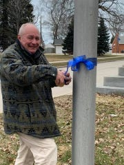 Curt Thoms, a retired health care worker of 35 years, is rallying his fellow citizens to purchase and put blue ribbons on trees, lampposts or anything they can near Holy Family Memorial hospital.