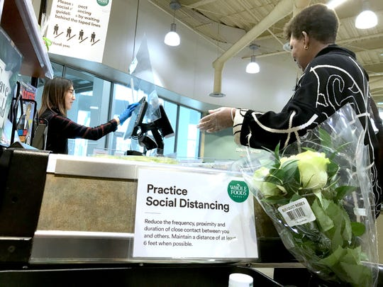 A sign encourages social distancing as a clerk rings up a customer at Whole Foods on North Prospect Avenue in Milwaukee.